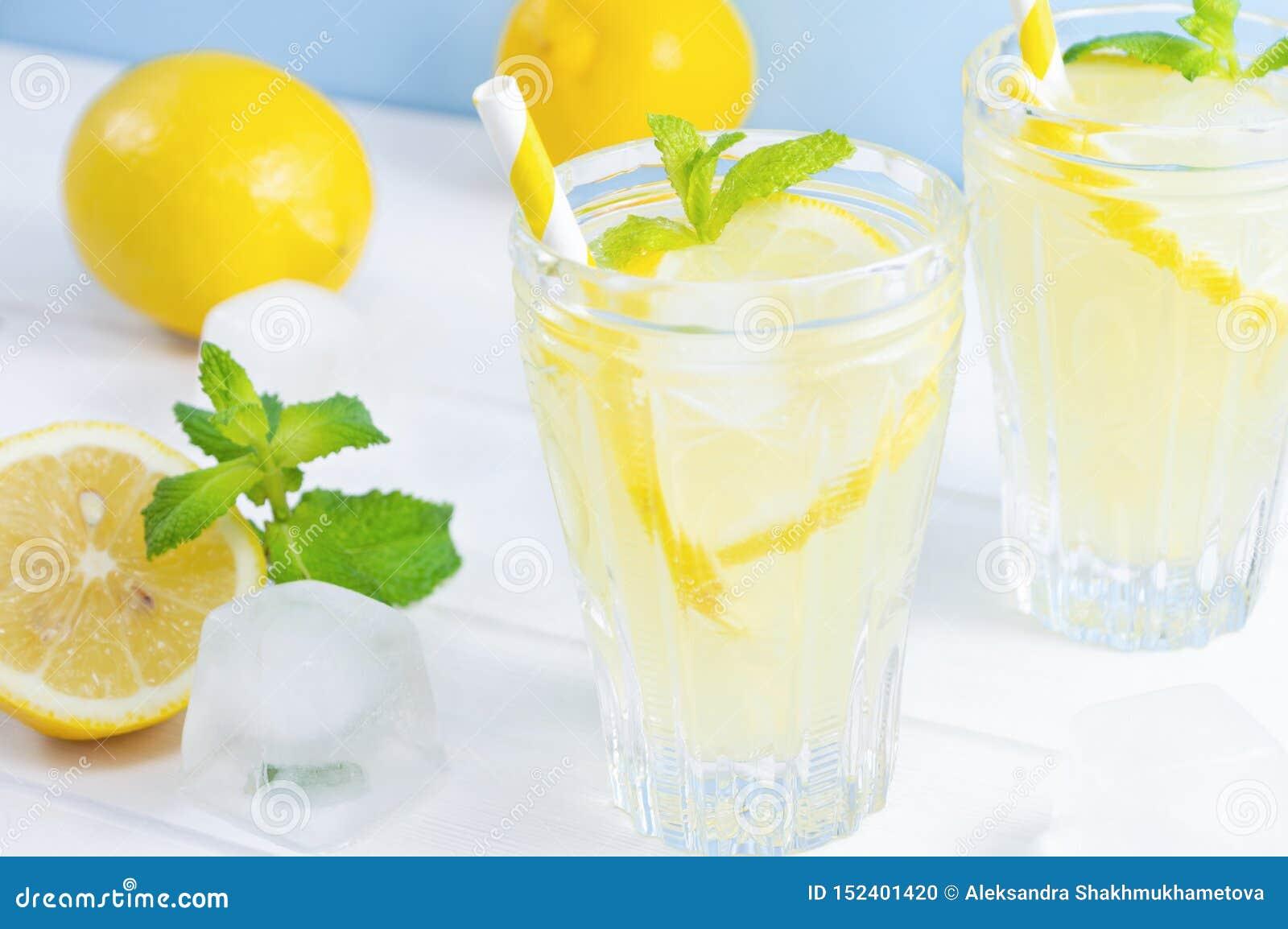 De glazen met de zomer drinken limonade, citroenfruit en muntbladeren op witte houten lijst