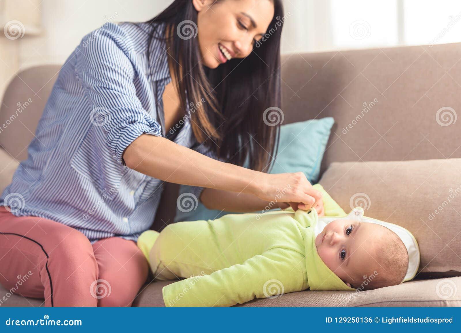 De glimlachende baby van de moeder kledende zuigeling omhoog