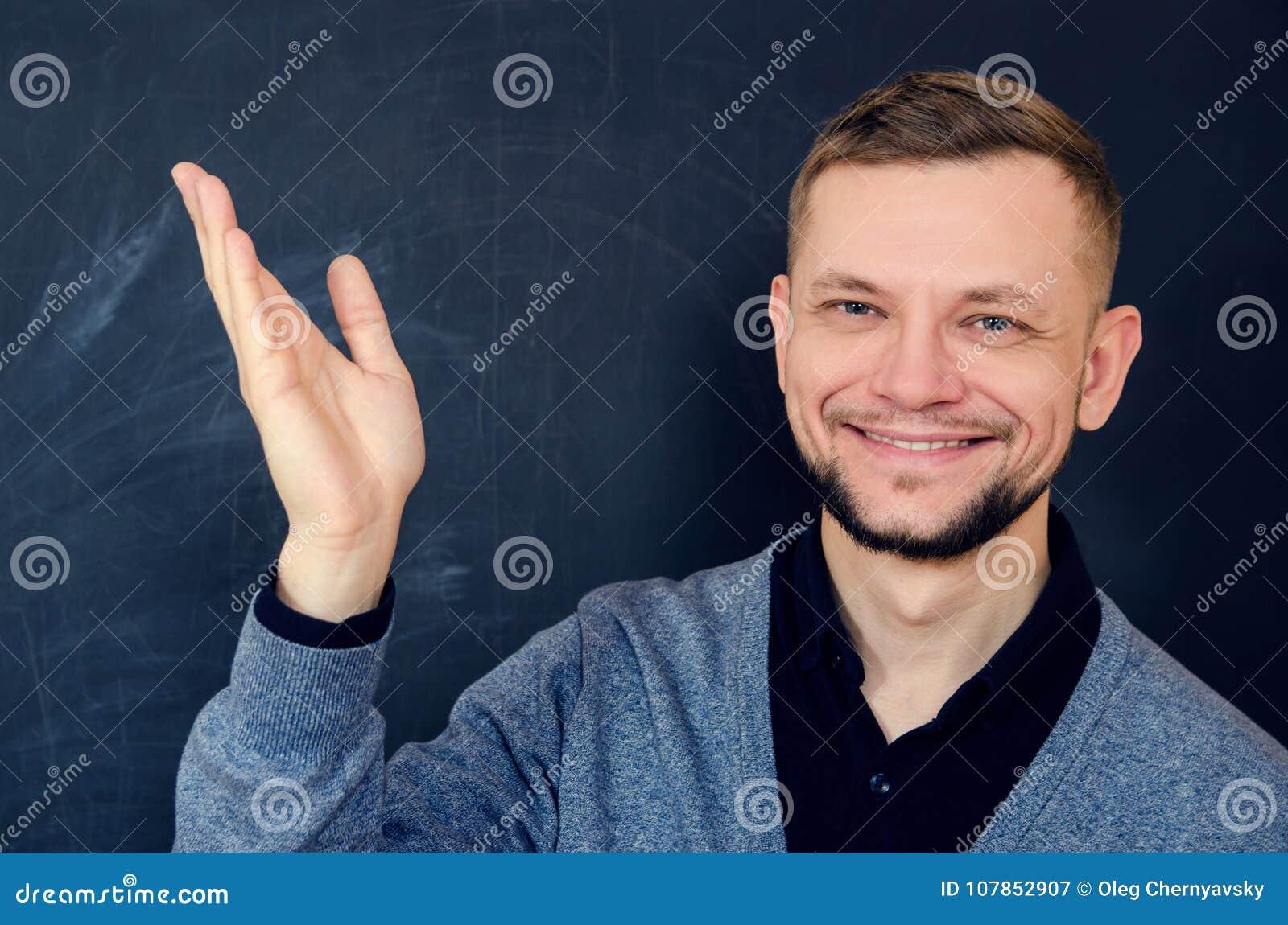 De glimlachende gebaarde mens maakt een welkom gebaar met een open hand