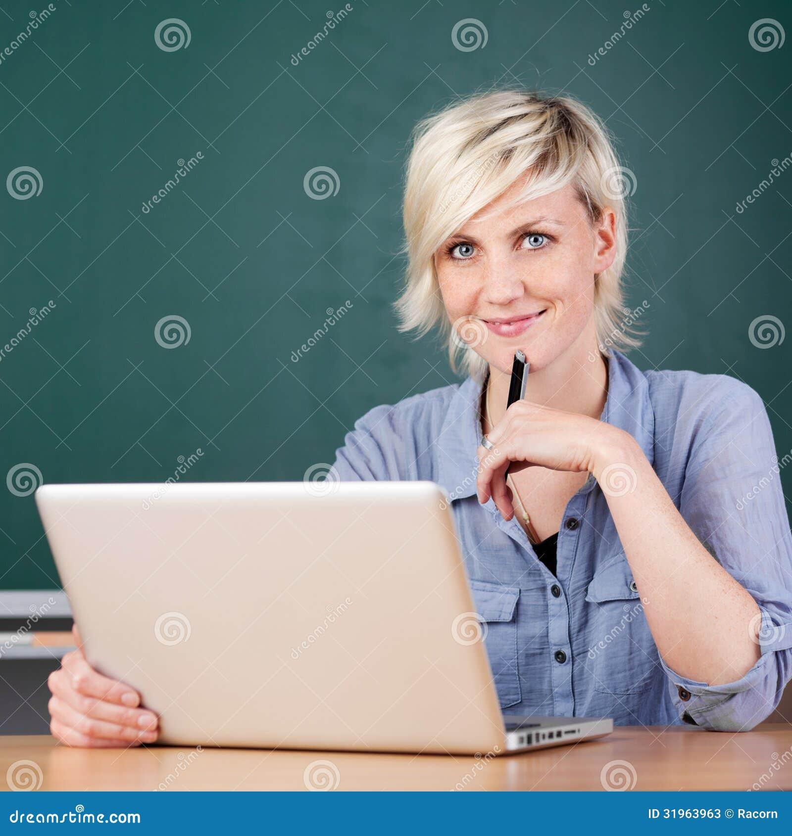 De glimlachende Jonge School van Leraarsusing laptop at
