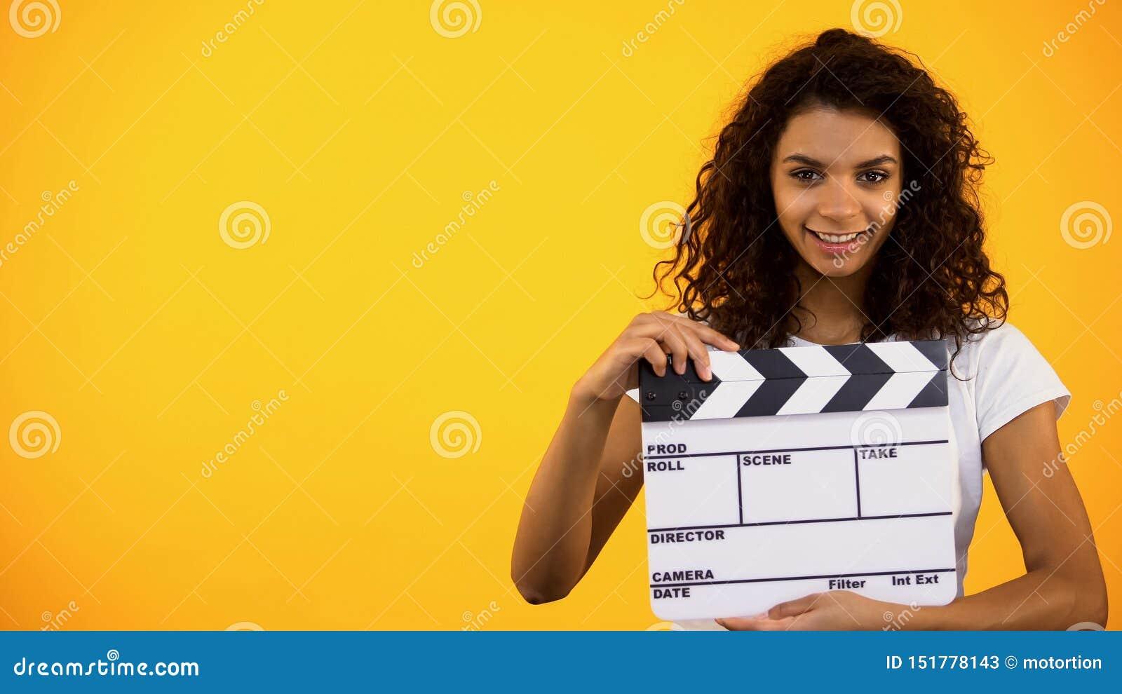 De glimlachende jonge vrouwelijke raad van de holdingsklep op oranje achtergrond, cinematografie