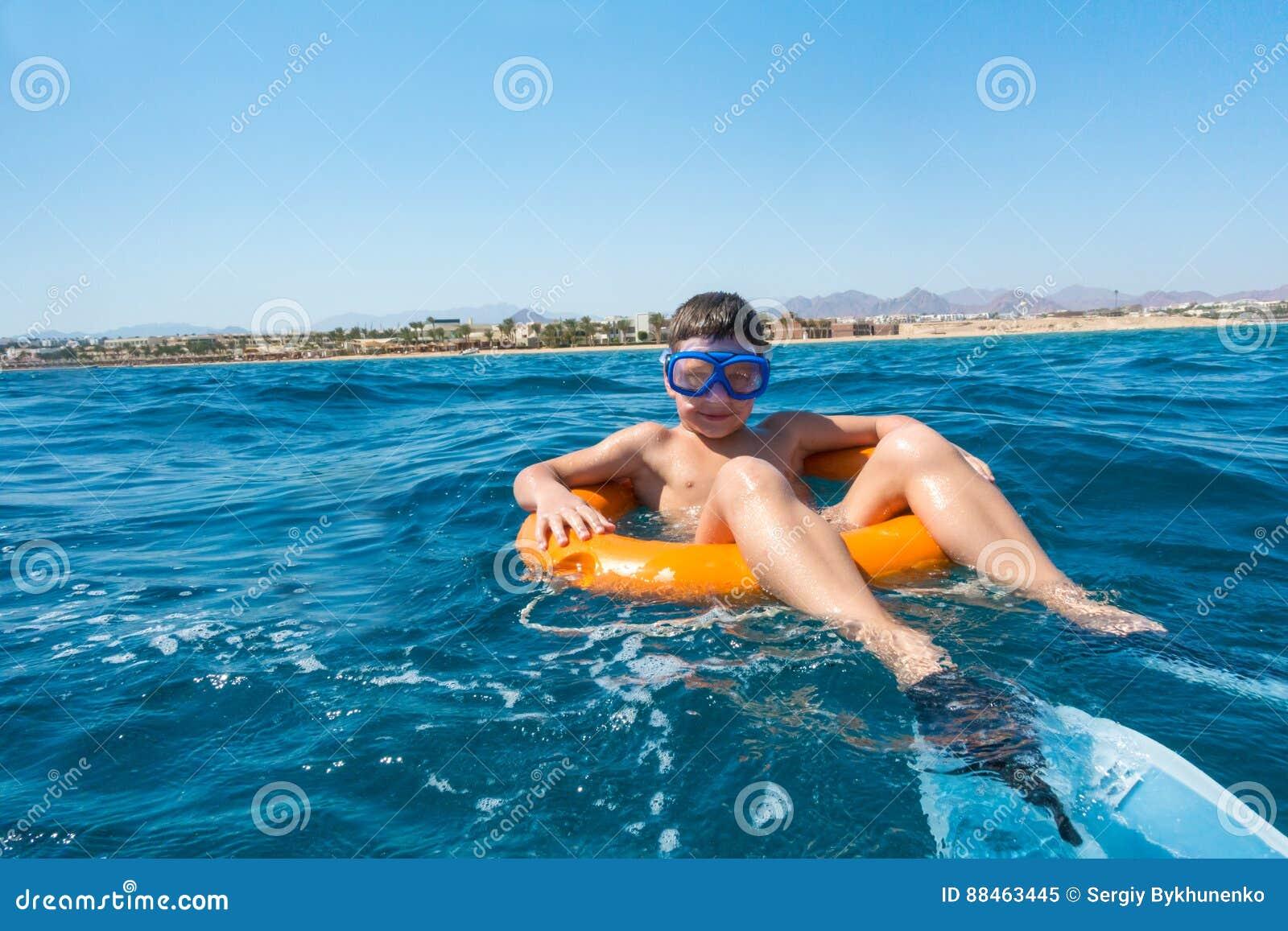 De glimlachende jongen leert om op reddingsboei in het overzees te zwemmen
