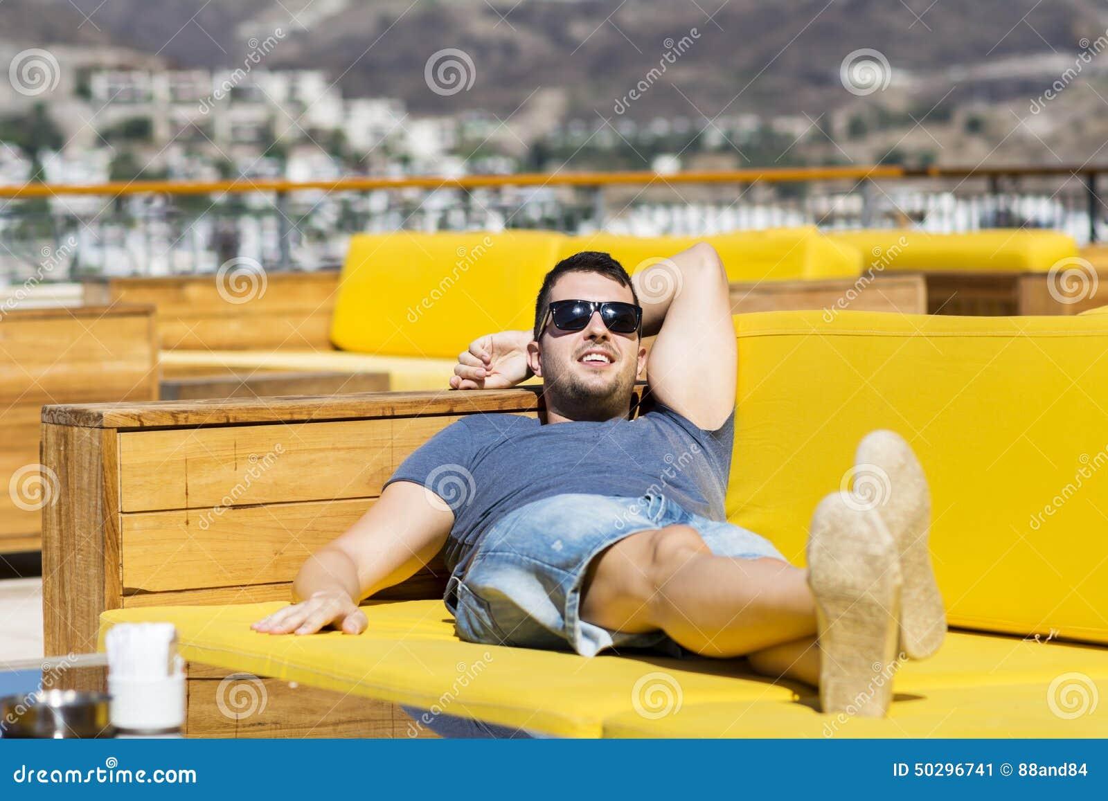 De glimlachende mens die van de de zomervakantie genieten die op a leggen sunbed in een overzeese bar