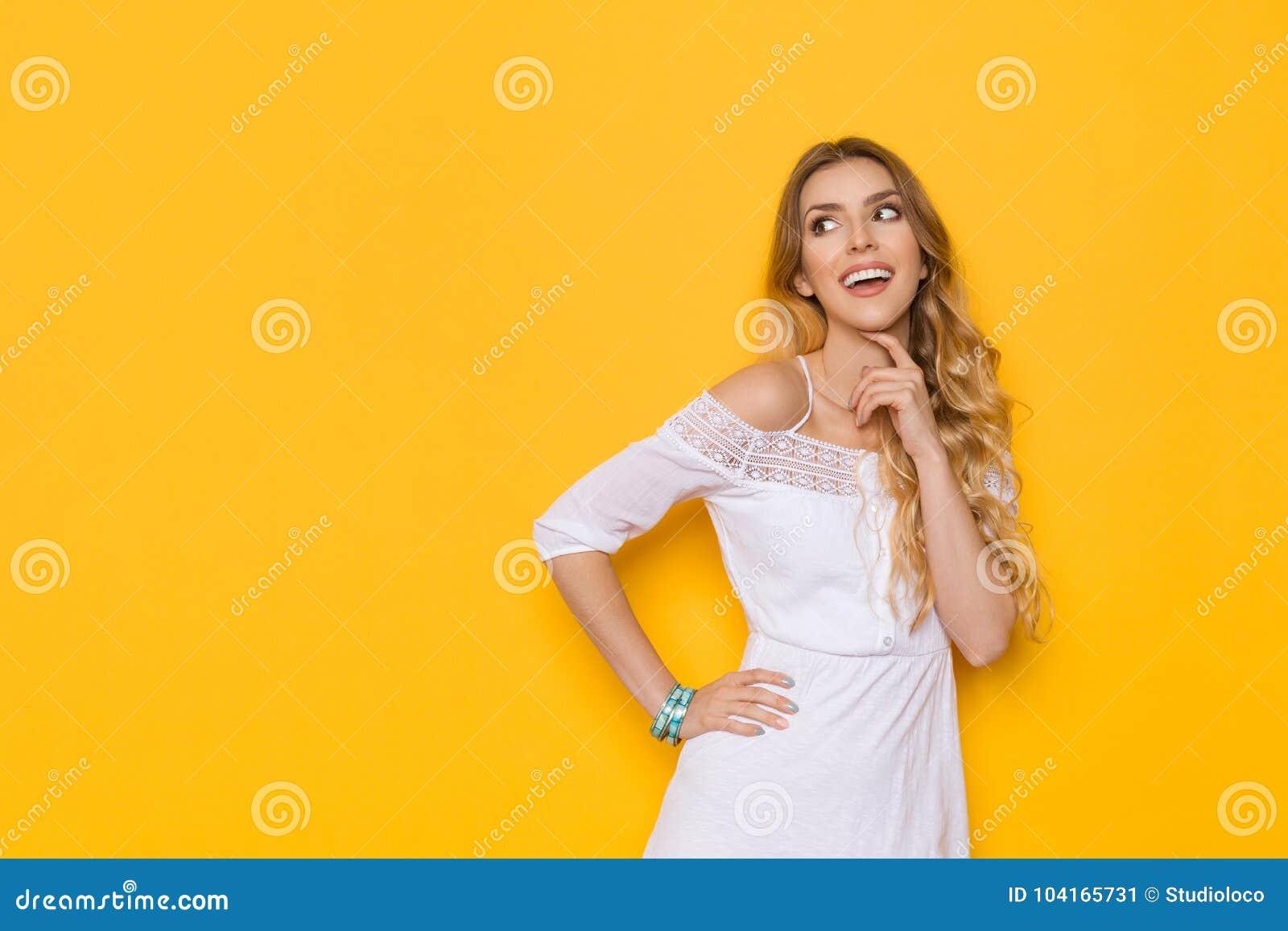 De glimlachende Mooie Blonde Jonge Vrouw in Witte de Zomerkleding kijkt weg en denkt