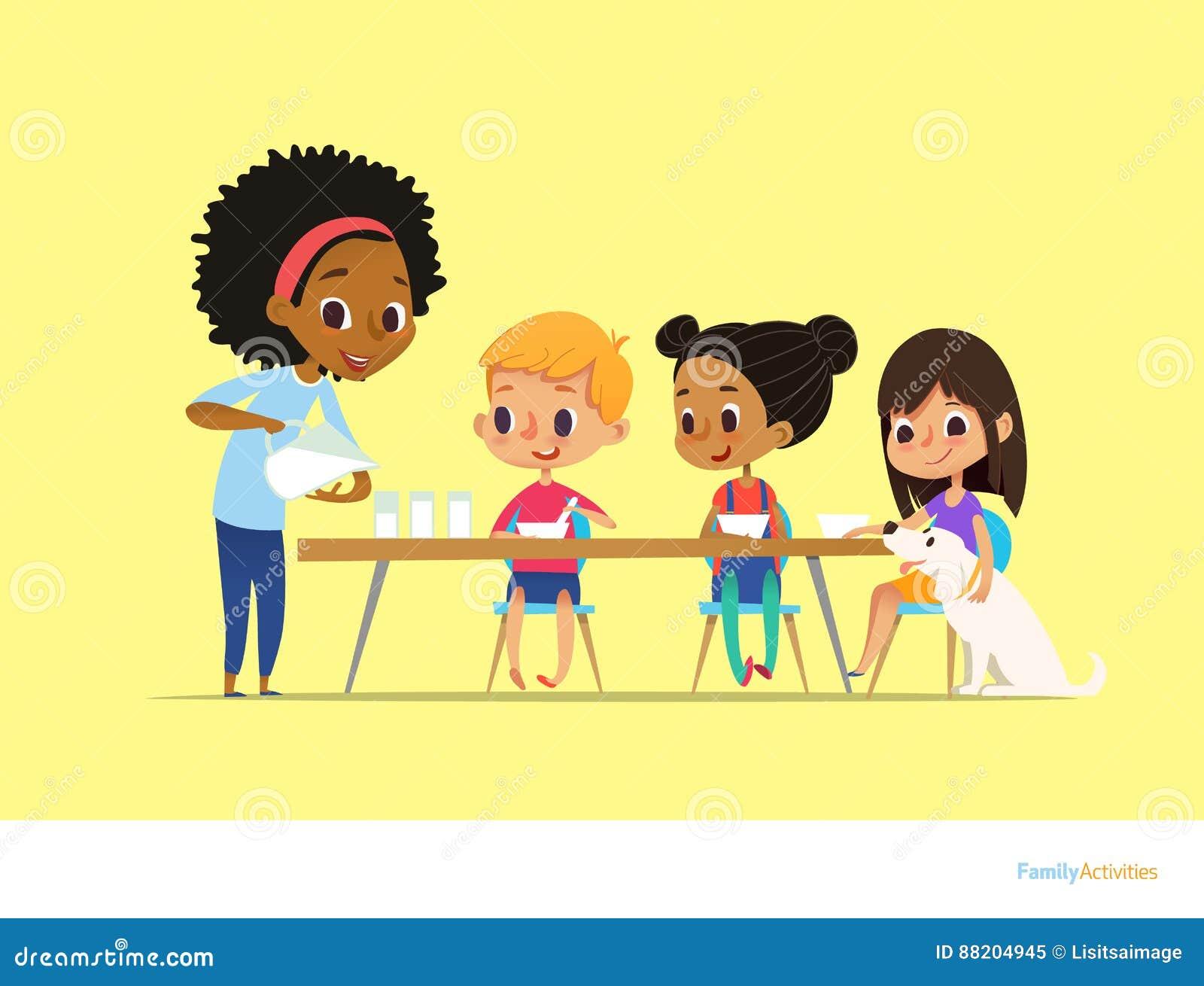 De glimlachende multiraciale kinderen zitten bij lijst en hebben ontbijt terwijl de moeder melk in gassen giet Jonge geitjes die