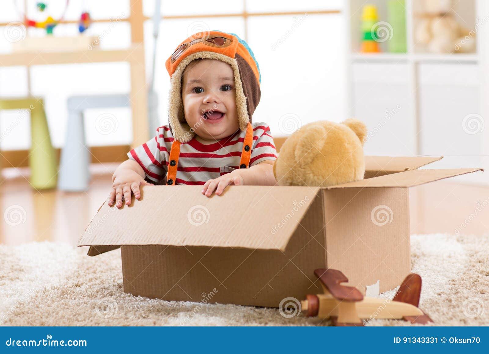 De glimlachende proefjongen van de vliegeniersbaby met teddybeerstuk speelgoed spelen in kartondoos