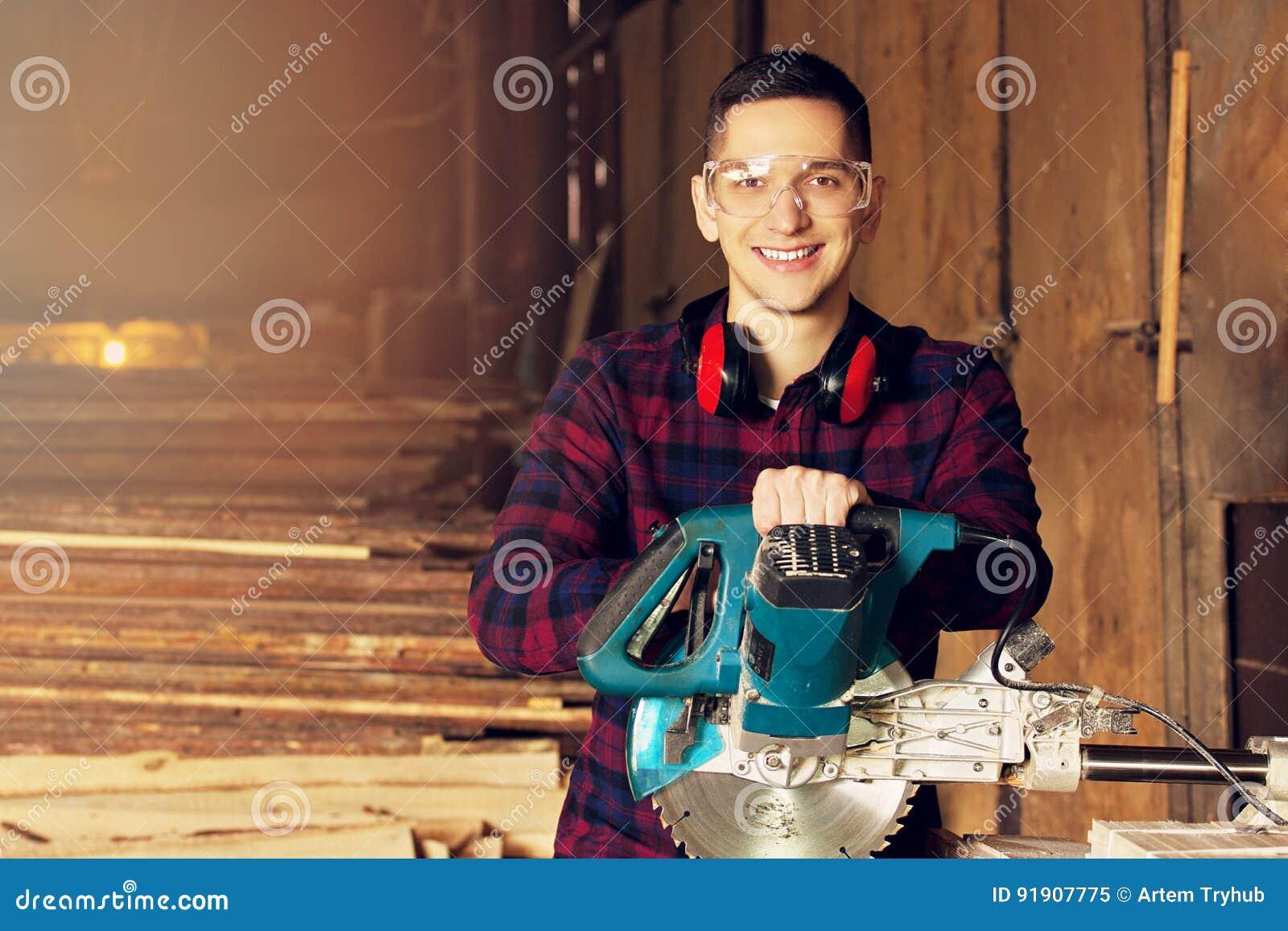 De glimlachende werkman kleedde zich in het geruite overhemd die met cirkelzaag bij de zaagmolen werken Hout op achtergrond