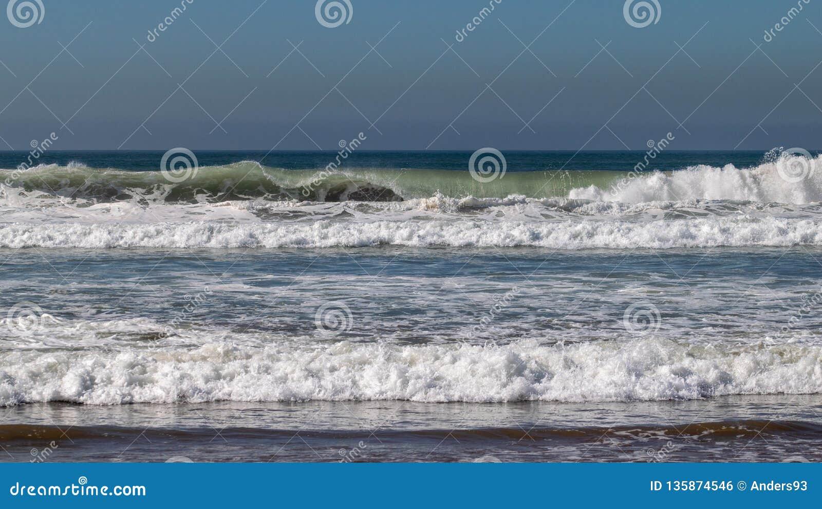 De golven die van de Atlantische Oceaan op zandstrand breken in Agadir, Marokko, Afrika