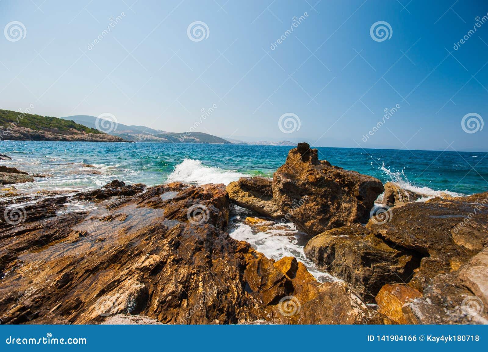 De golven slaan op de rotsen, de overzeese woede op de stenen
