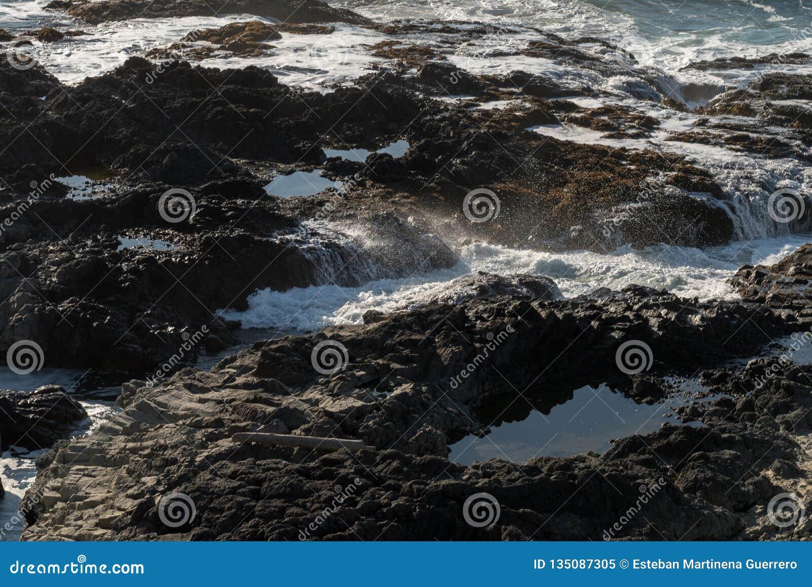 De golven verpletteren op de rotsen van de kust bij Speciaal de Rentegebied van Kaapperpetua waar Thor goed wordt gevestigd