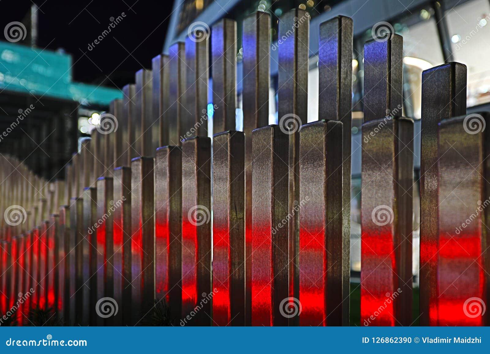 De golvende houten omheining dichtbij de weg in de kleuren van autoverkeerslichten