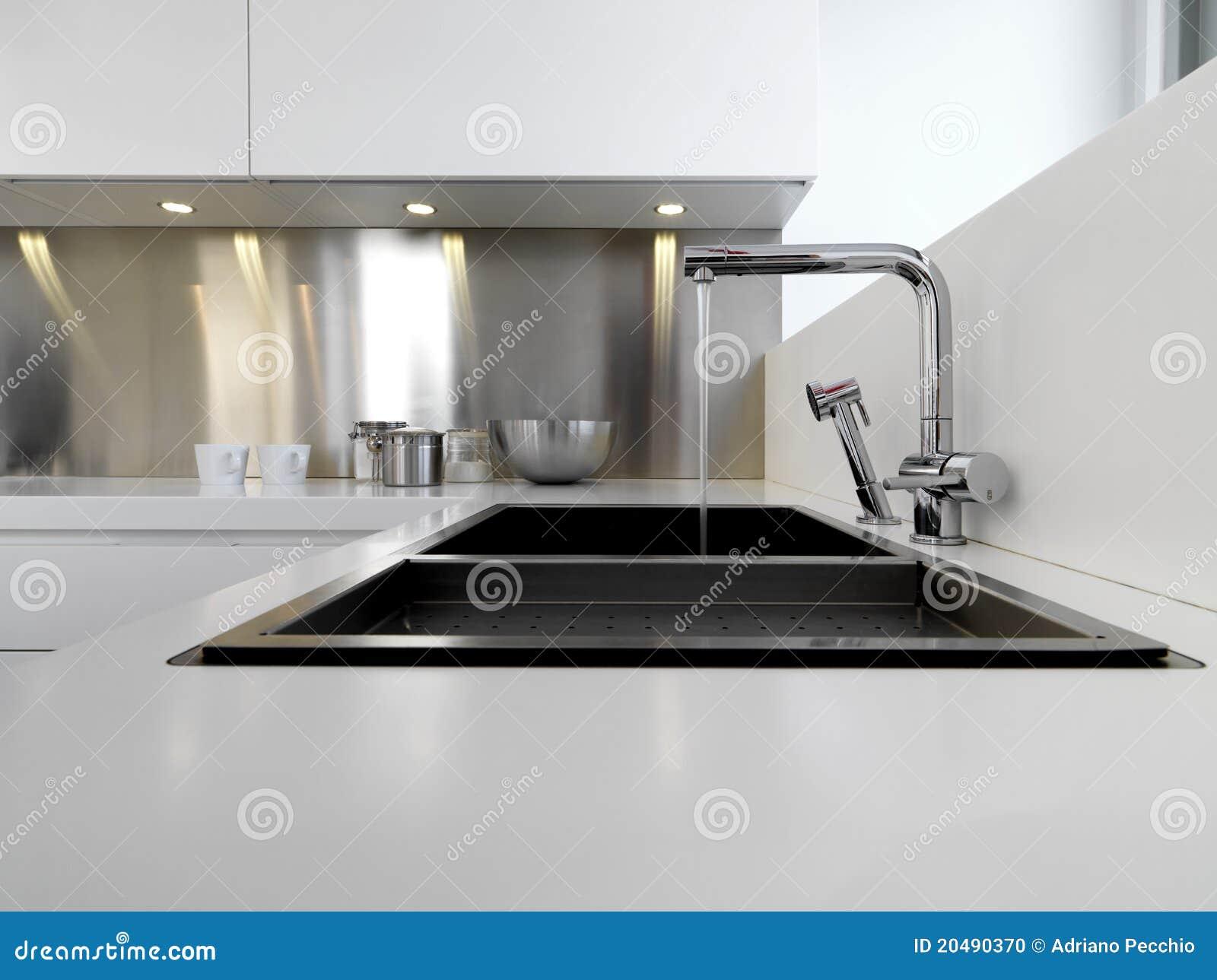 De gootsteen en de kraan van het staal in de moderne keuken stock
