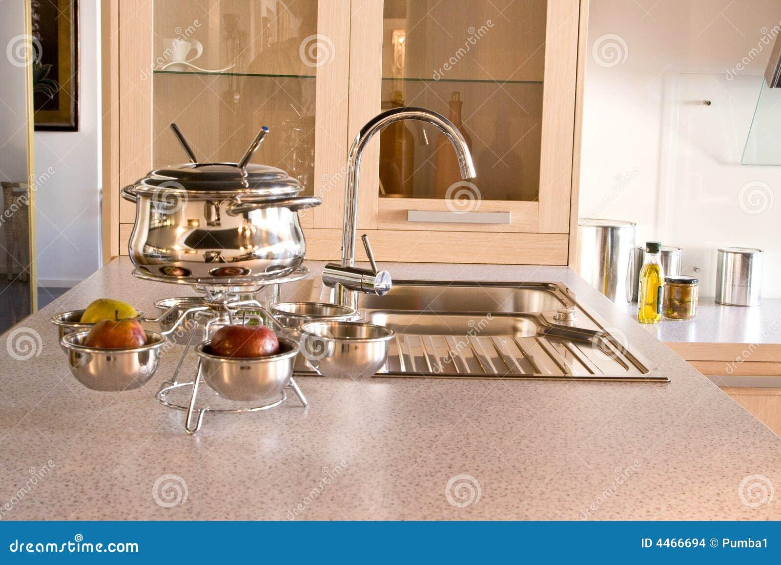 De gootsteen van de keuken met de kraan en Werktuigen voor fondu