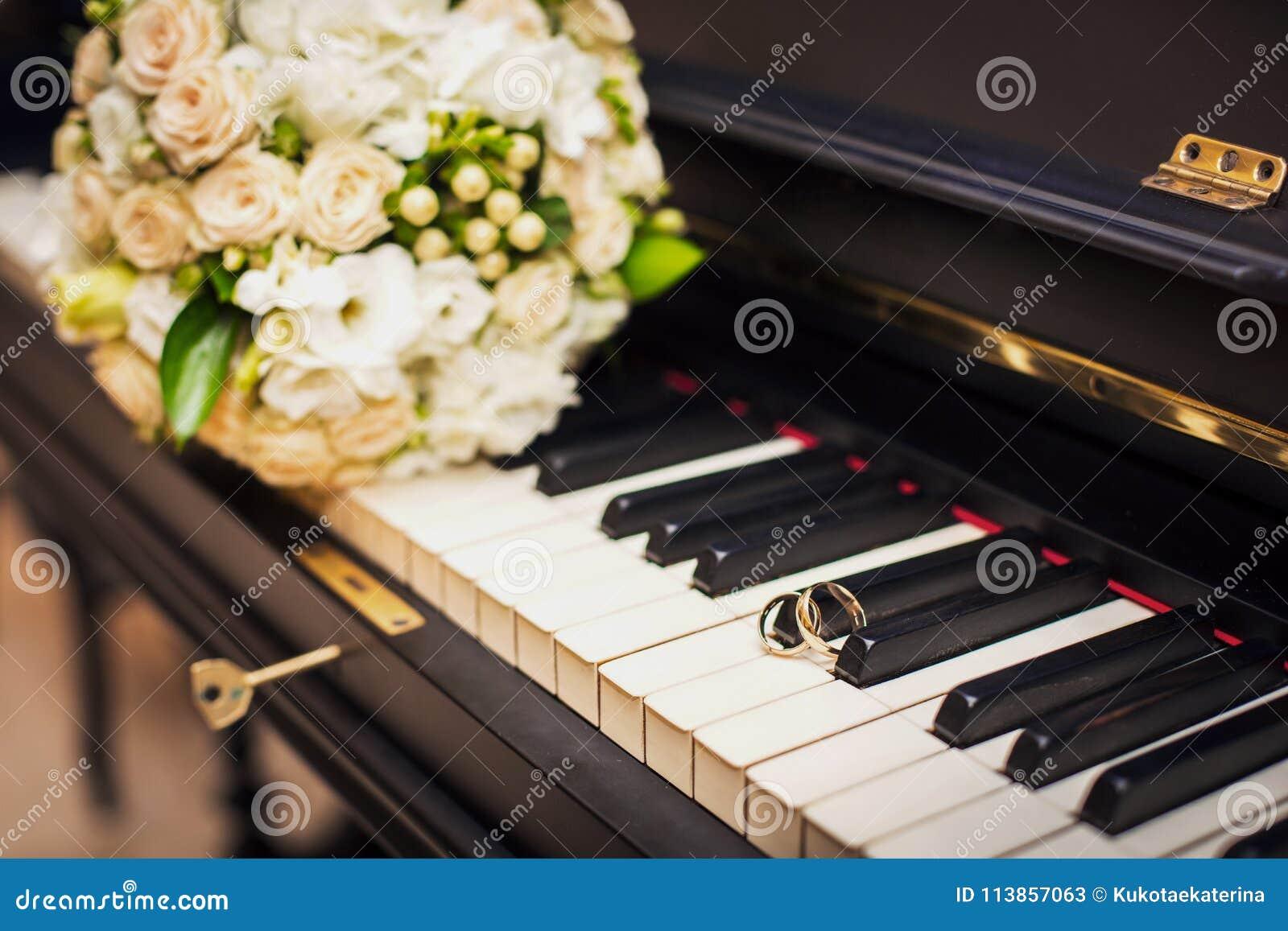 De gouden bruiloftringen liggen op de piano