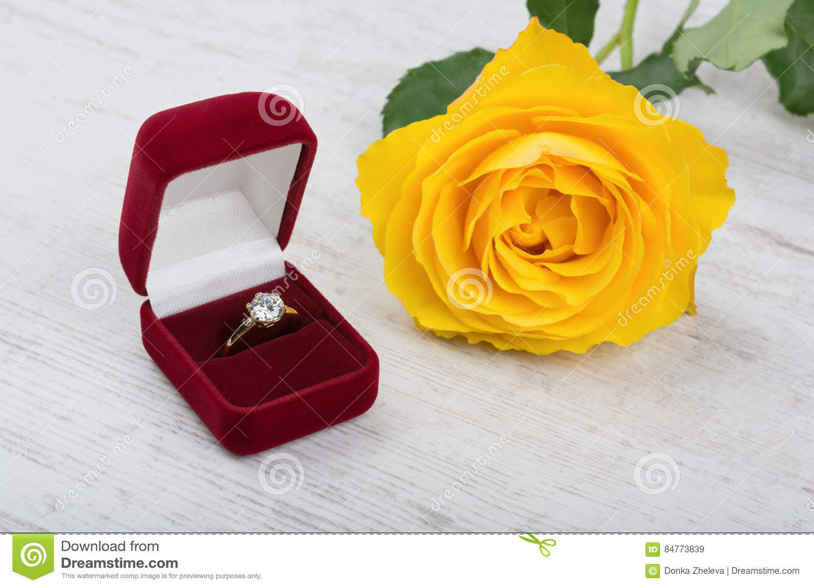 De gouden parelring in een rode giftdoos en geel nam op witte houten achtergrond toe