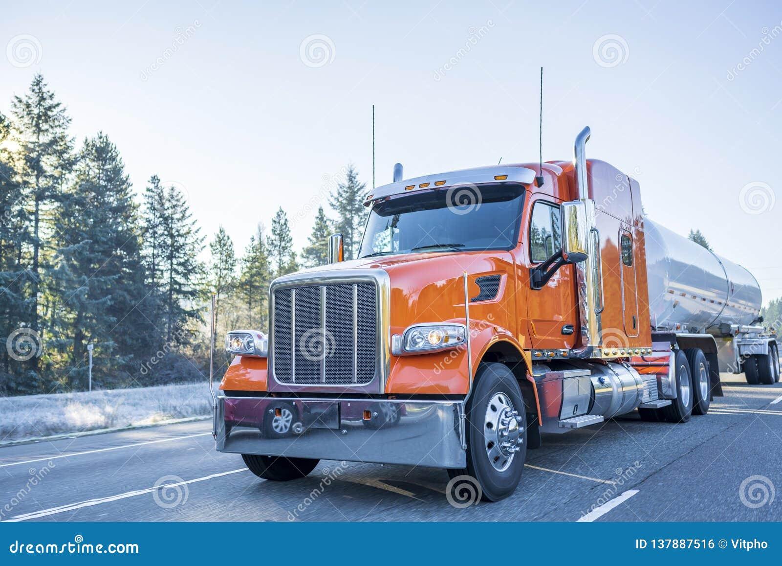 De grande installation d Américain camion classique orange semi transportant la cargaison liquide dans la remorque de réservoir s