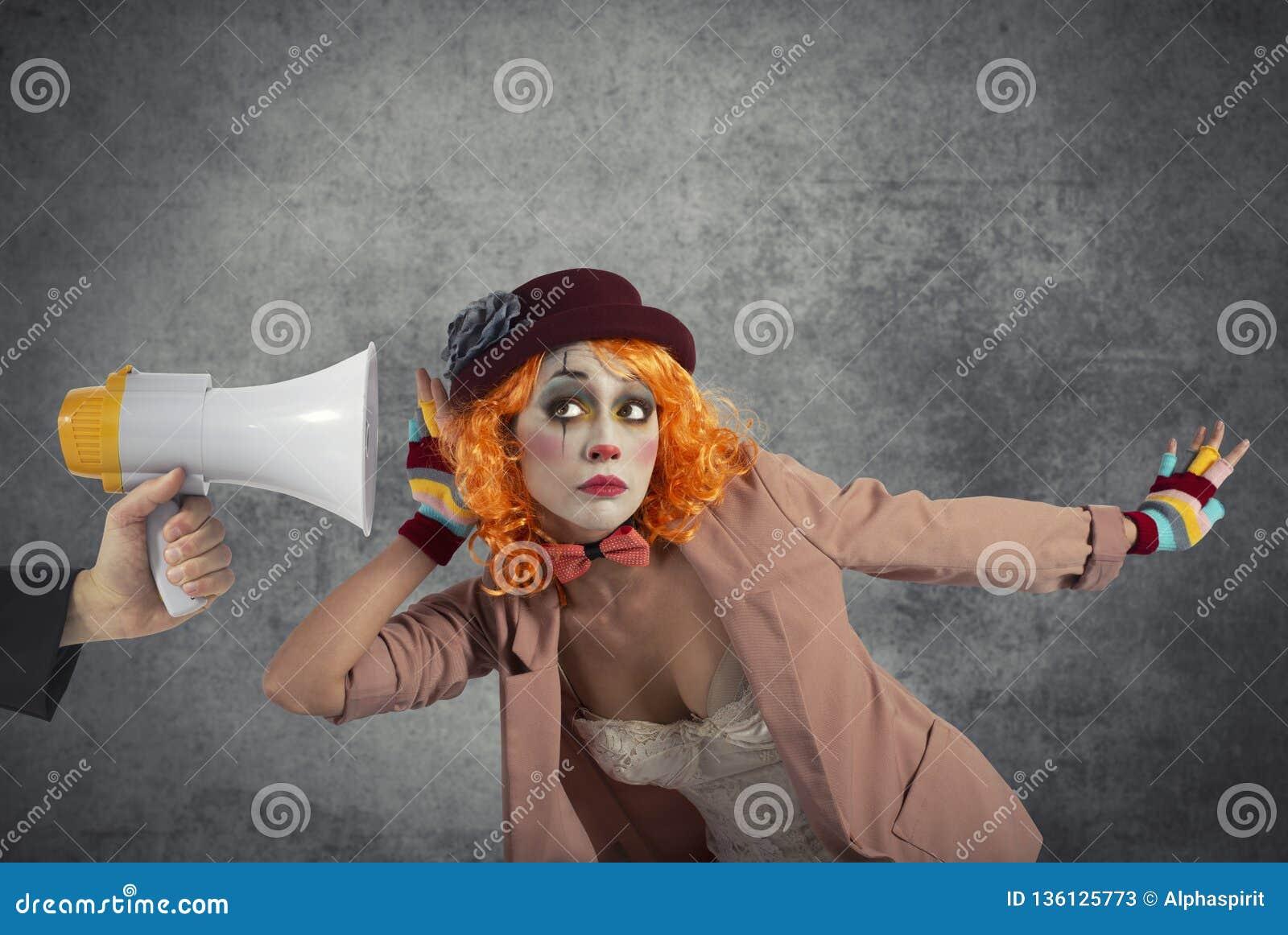 De grappige clown hoort een megafoon met een bericht