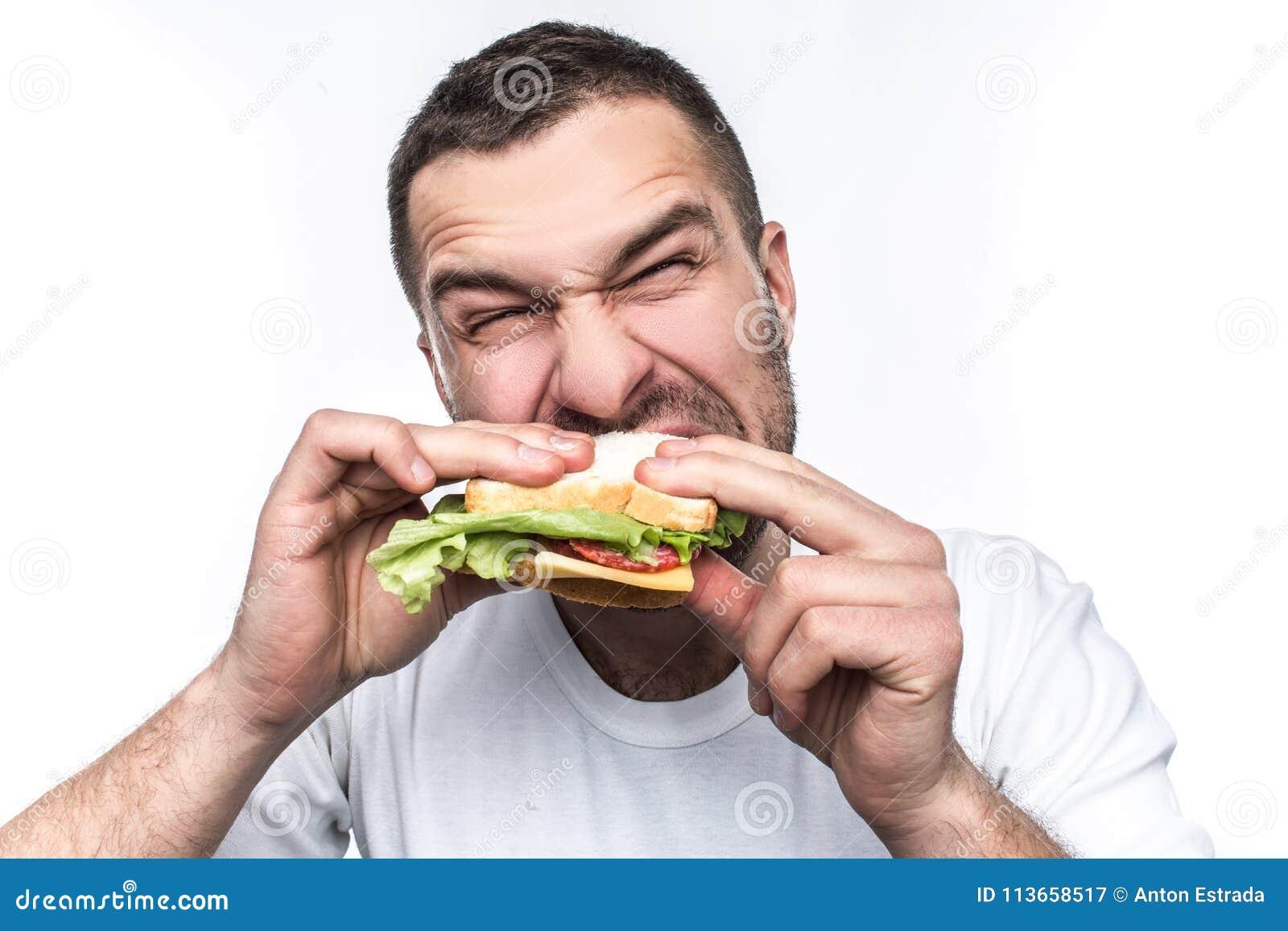 De grappige en hongerige kerel eet wat snel voedsel Hij is hongerig als een wolf De mens bijt zeer harde sandwich geïsoleerde