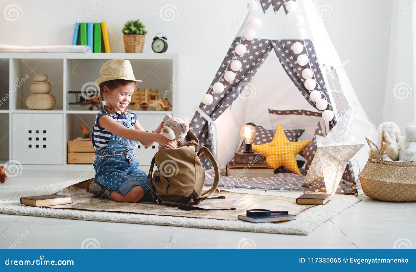 De grappige toerist van het kindmeisje met wereldkaart, rugzak en meer magnifier