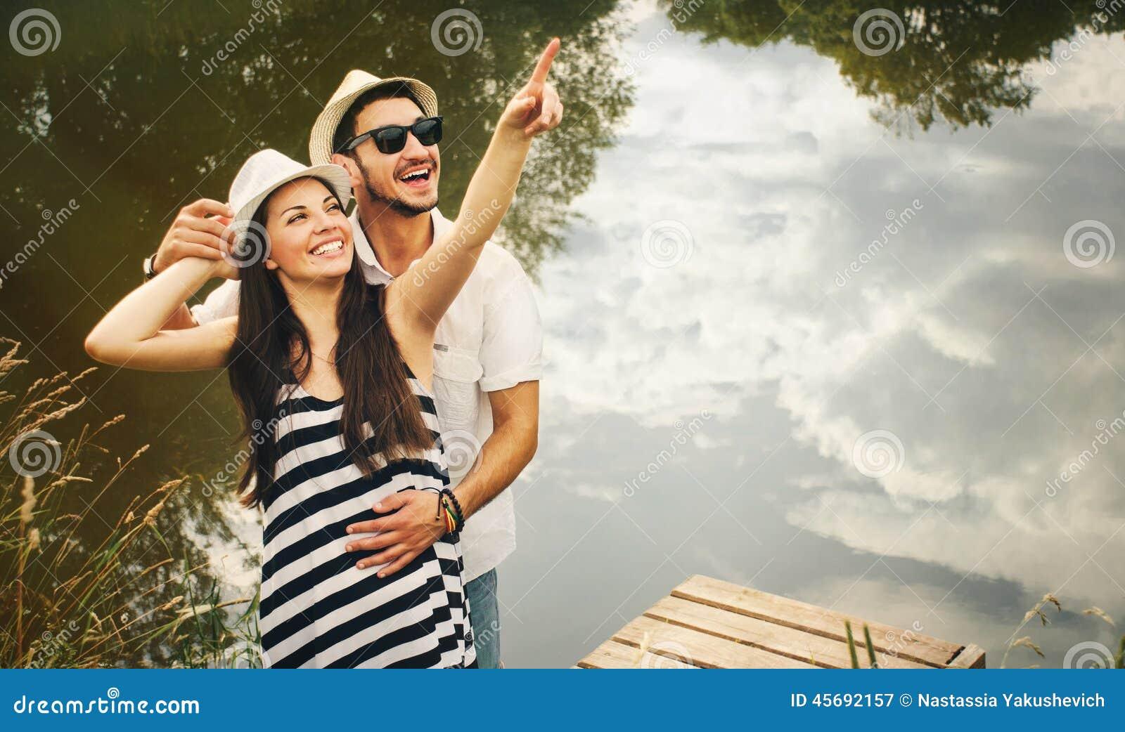 De greep van gelukkig romantisch paar op pijler onderzoekt de wereld van is