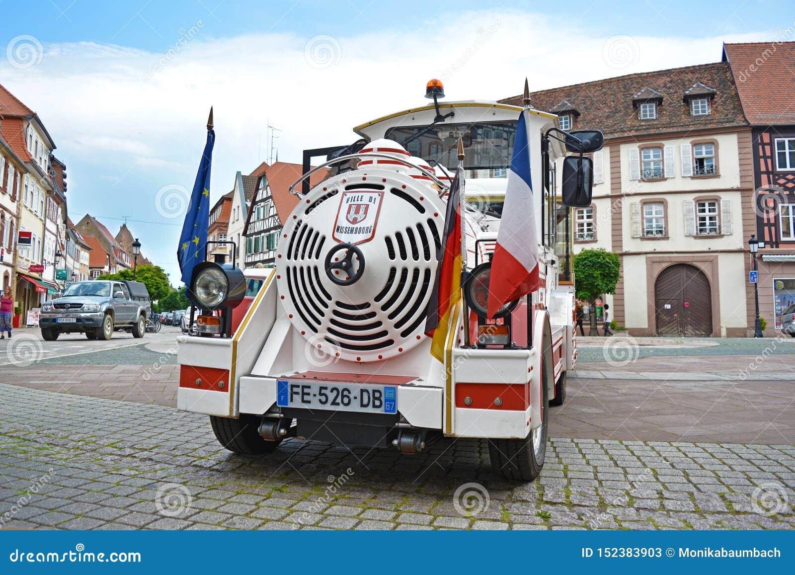 De grensreis met witte toeristische minitrein vormde auto met Duitse en Franse vlag in voorzijde, die zich op marktvierkant bevin