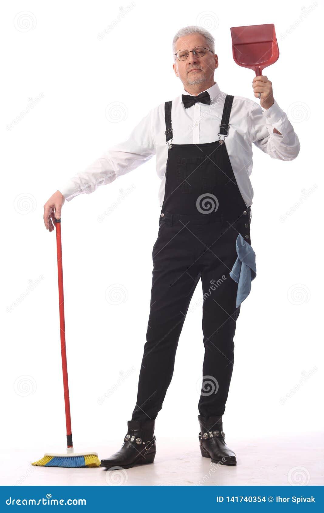 De grijs-haired reinigingsmachine, de portier in een zwarte jumpsuit met een zwabber en het blik verlenen de schoonmakende dienst
