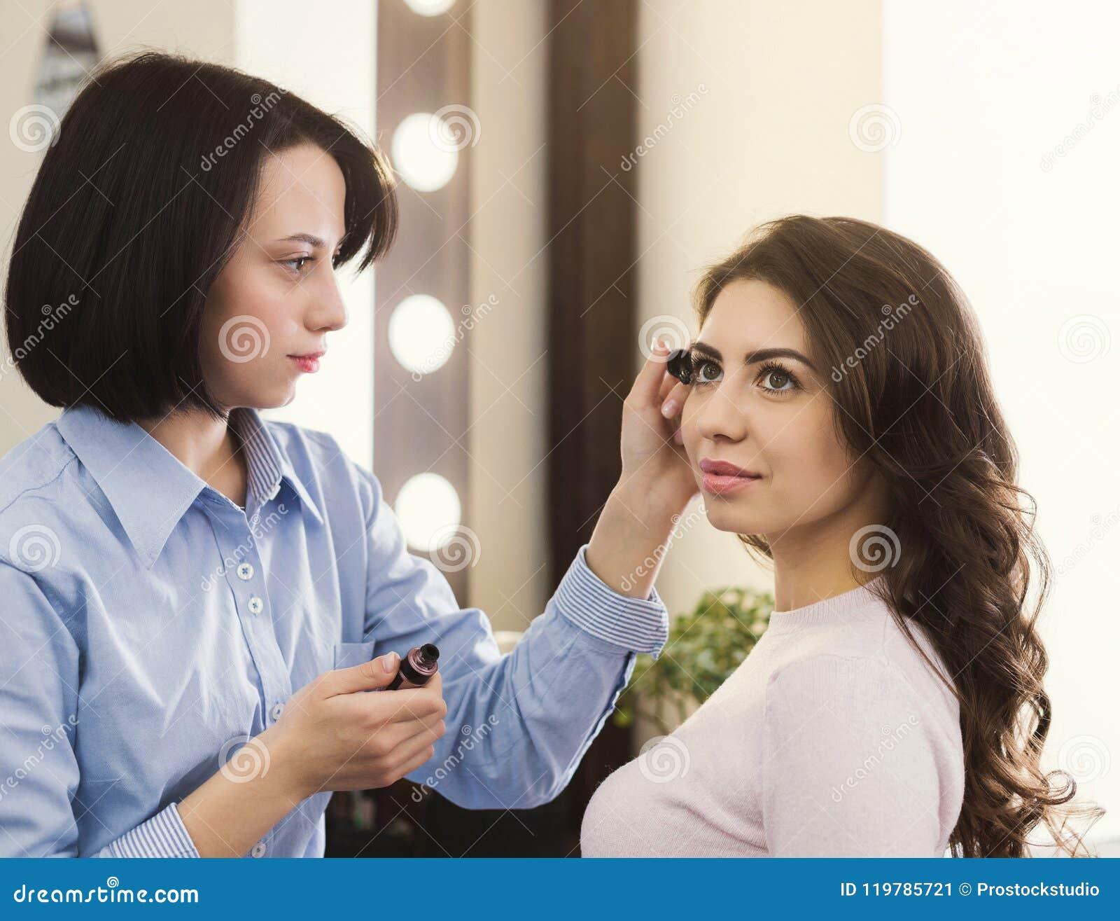 De grimeur maakt omhoog wimpers voor mooi meisje
