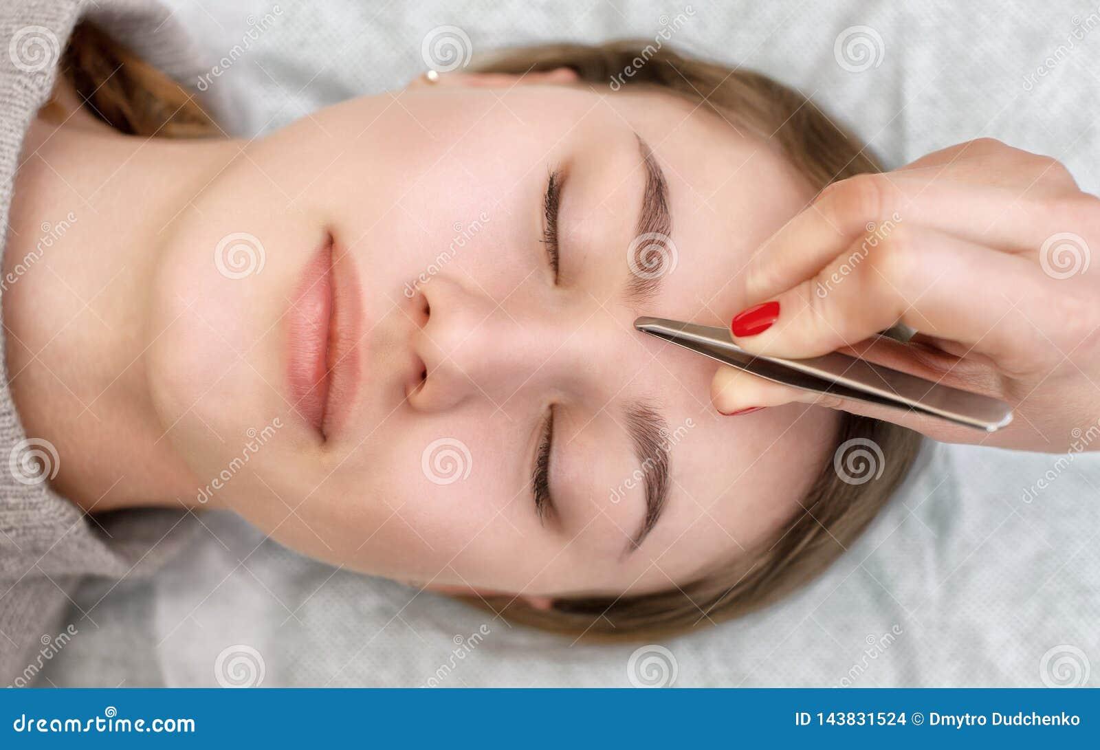 De grimeur plukt haar wenkbrauwen van een jonge vrouw in een schoonheidssalon