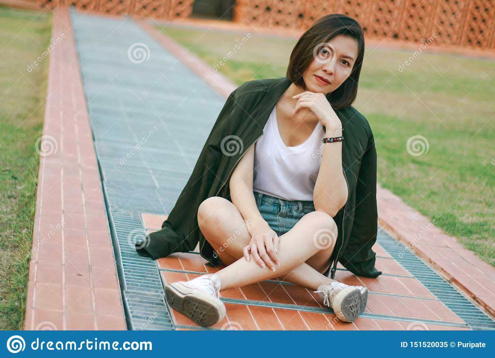 De groene zitting van de overhemdsvrouw op het gazon