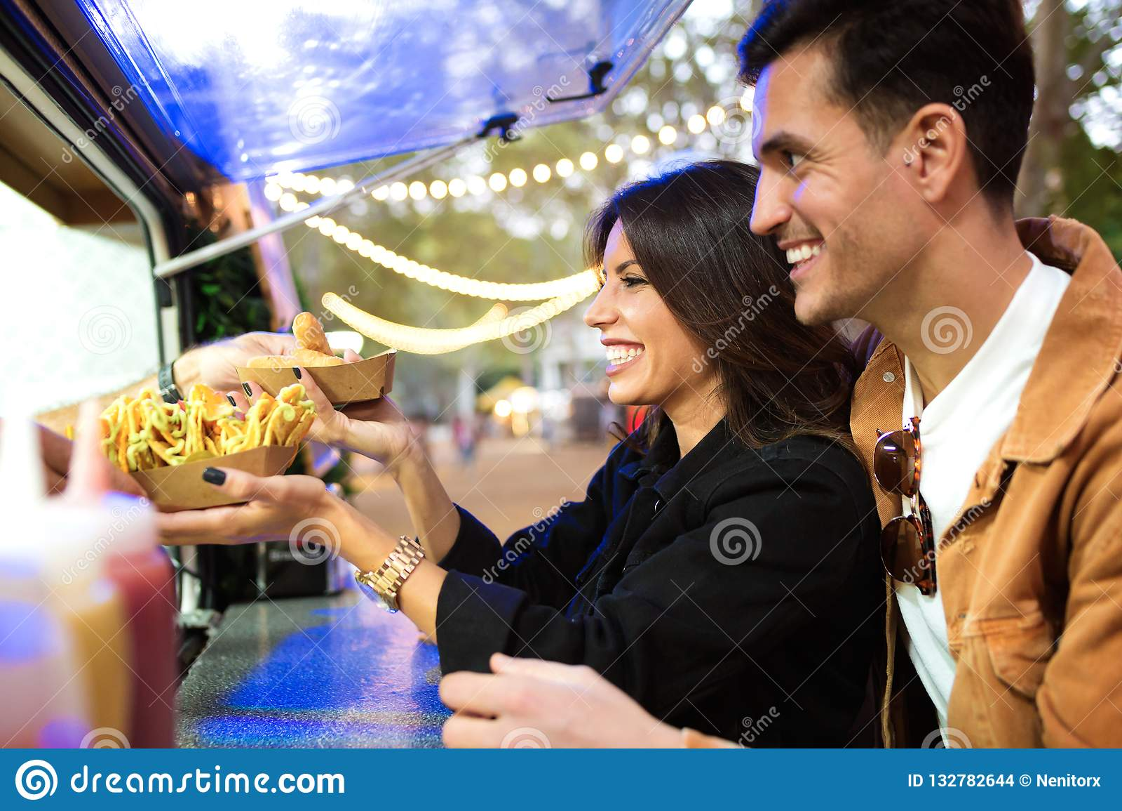 De groep aantrekkelijke jonge vrienden die en verschillende types van snel voedsel kiezen kopen eet binnen markt in de straat