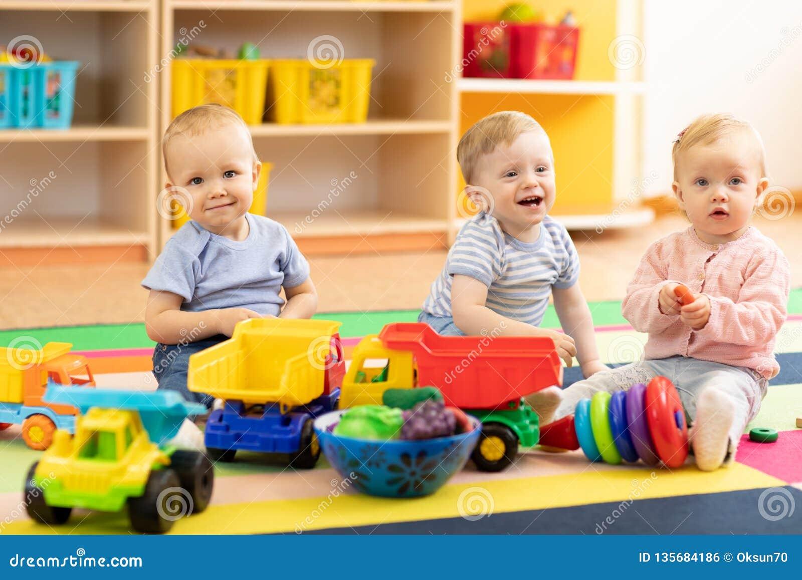 De groep babys speelt op vloer in kinderdagverblijf De kinderen in de opvang centreren Pret in de kinderen` s speelkamer