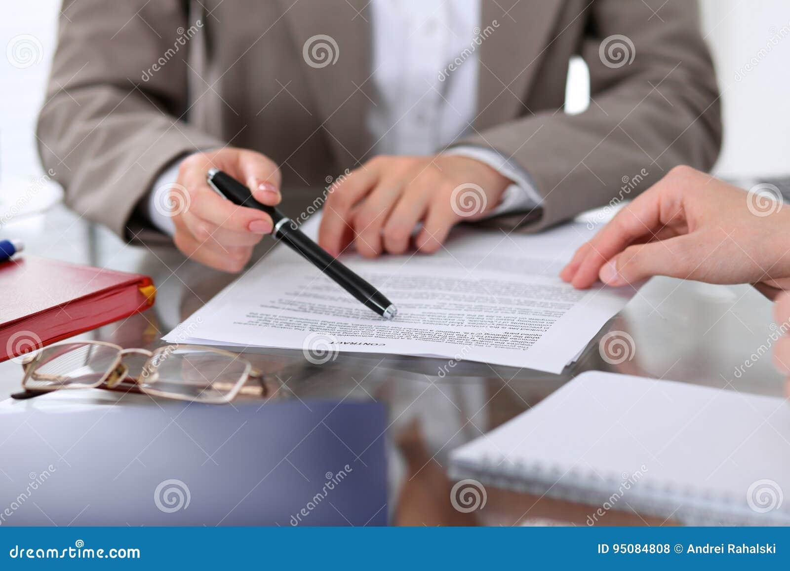 De groep bedrijfsmensen en advocaten die contractdocumenten bespreken die bij de lijst zitten, sluit omhoog