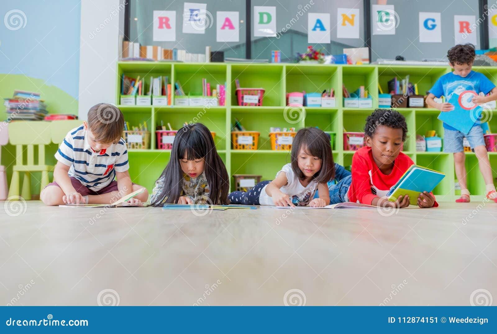 De groep diversiteitsjong geitje bepaalt op vloer en boek i van het lezingsverhaal