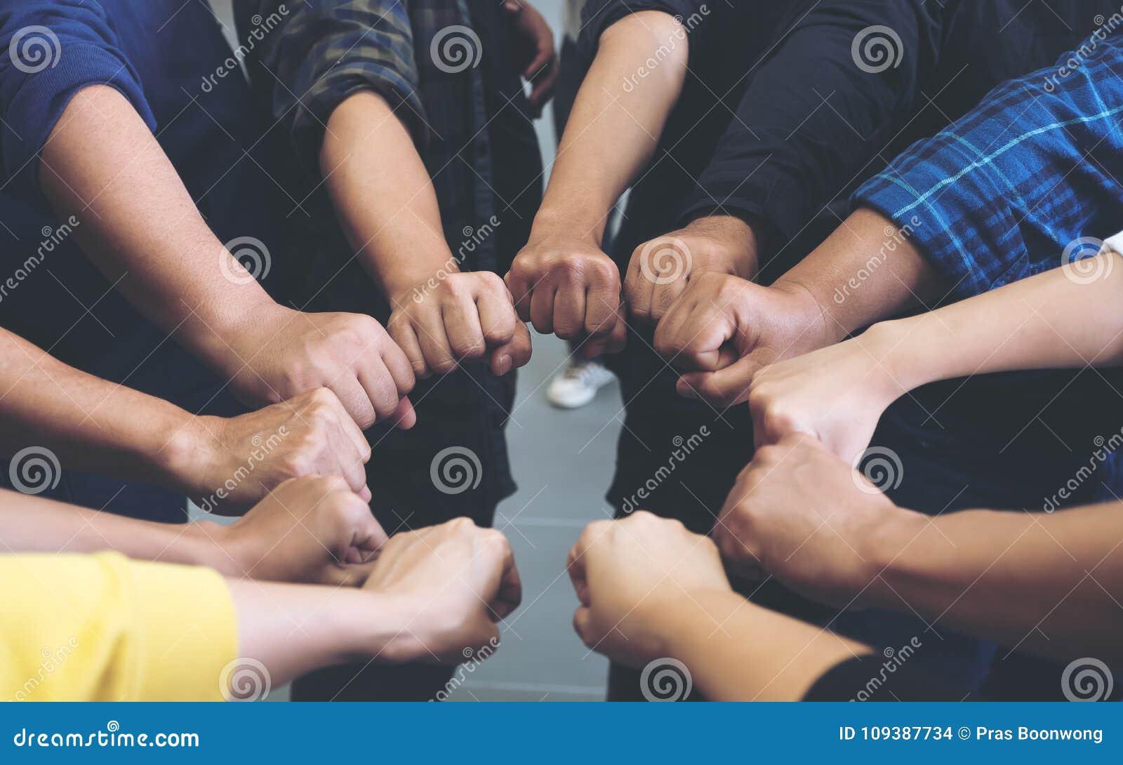 De groep het commerciële teamwerk sluit zich aan bij hun handen samen met macht en succesvol