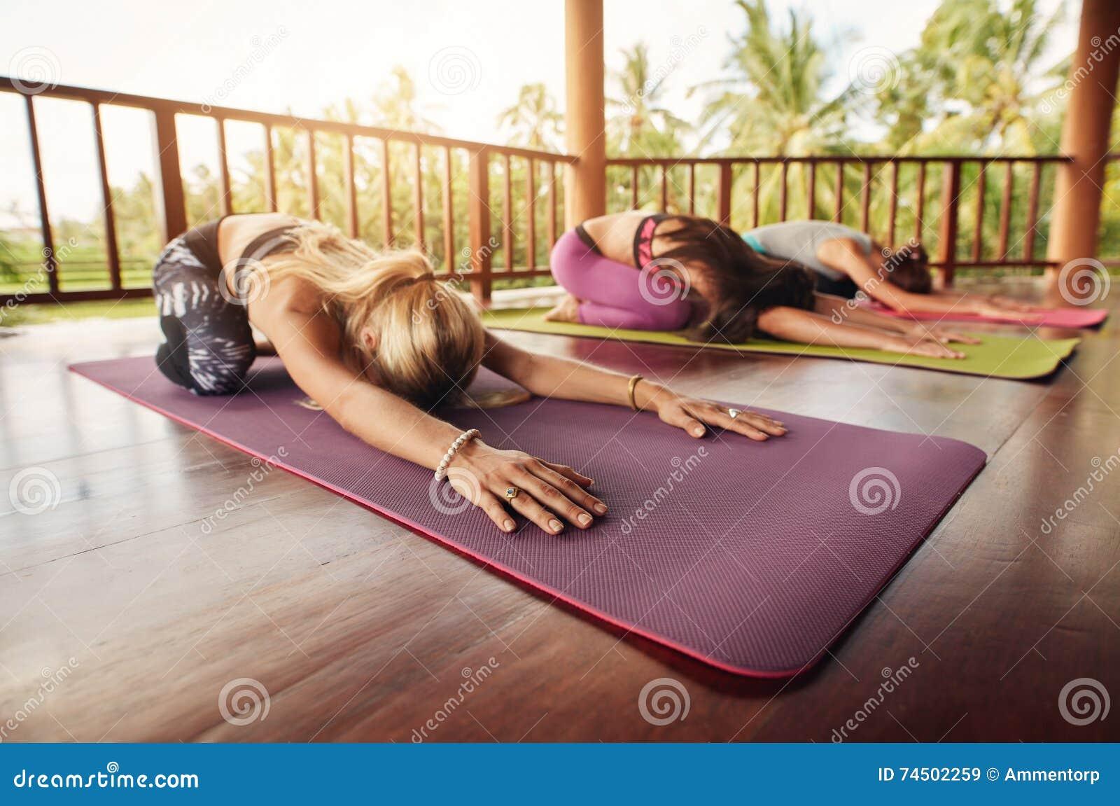 De groep jonge vrouwen die kind doen stelt yoga