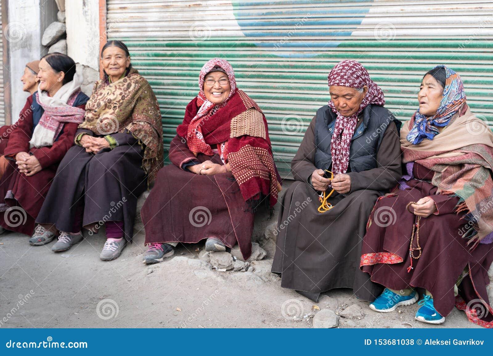 De groep Leh-vrouwenzitting voor de ingang aan het klooster