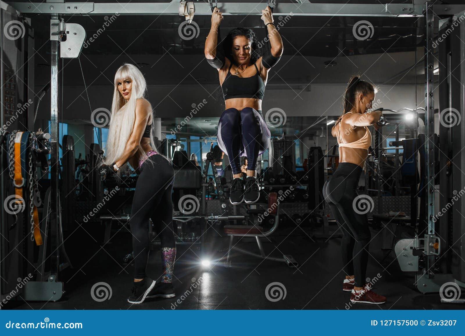 De groep meisjes leidt met TRX-riemen en hogere toi van de blok parallelle greep de borst in de gymnastiek op Zij dragen