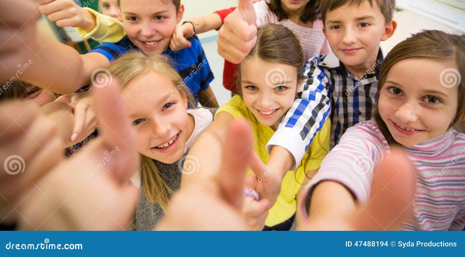 De groep schooljonge geitjes het tonen beduimelt omhoog
