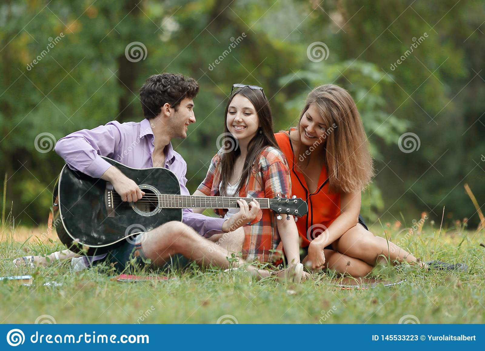 De groep studenten met een gitaar ontspant zitting op het gras in het stadspark