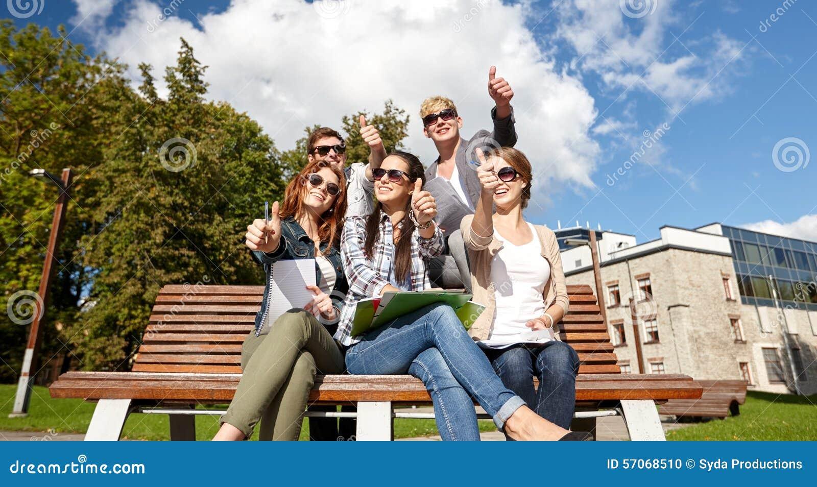 De groep studenten of tieners het tonen beduimelt omhoog