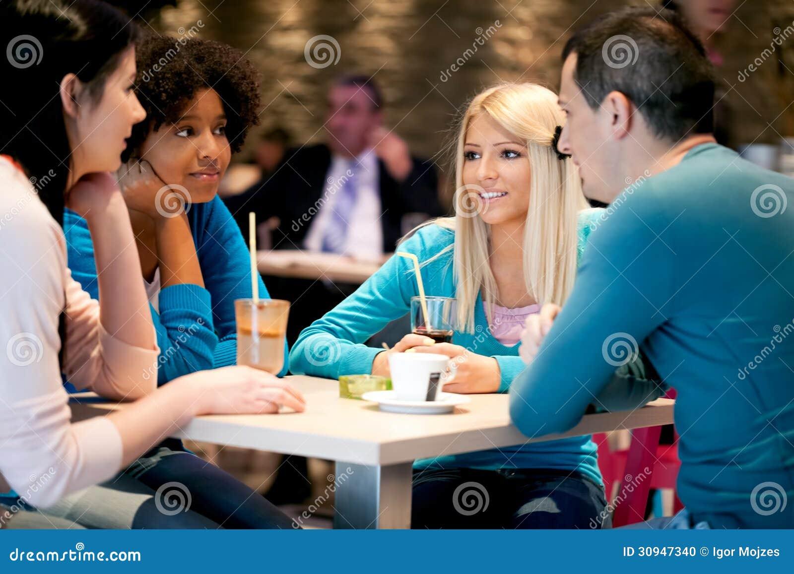 De groep tieners in een koffie geniet van