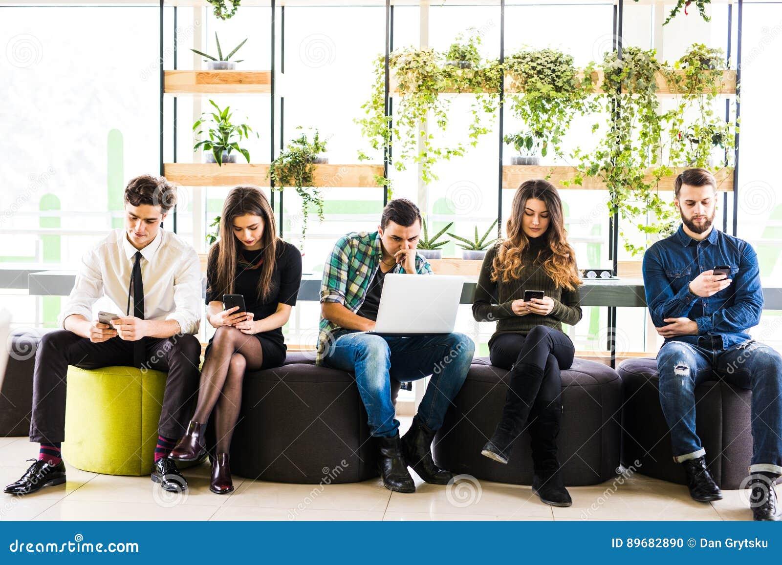 De groep vrienden die op stoelen dichtbij elkaar zitten en iedereen gebruiken zijn divices in moderne bureauruimte Samen pret in