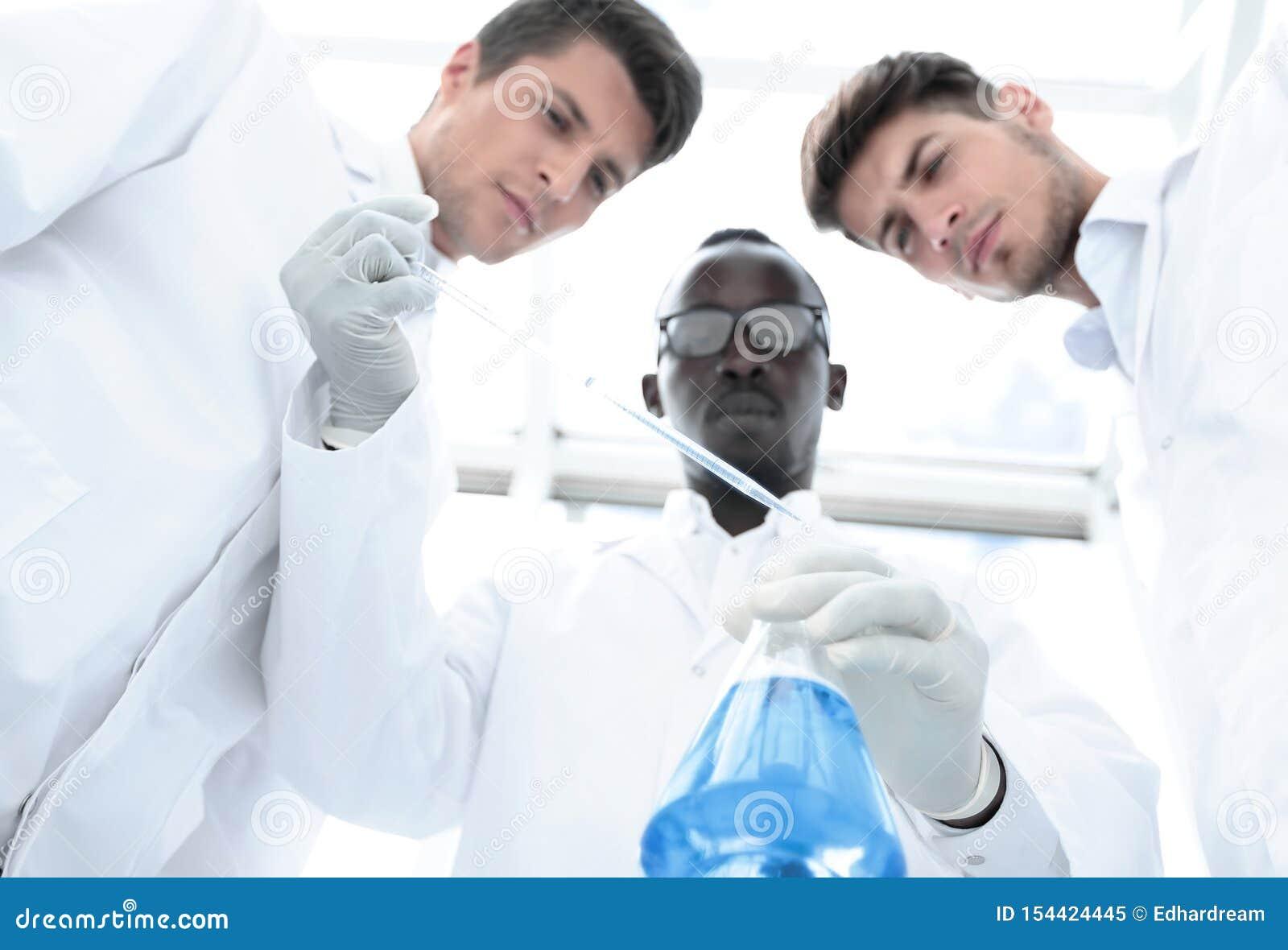 De groep wetenschappers onderzoekt de vloeistof in de fles