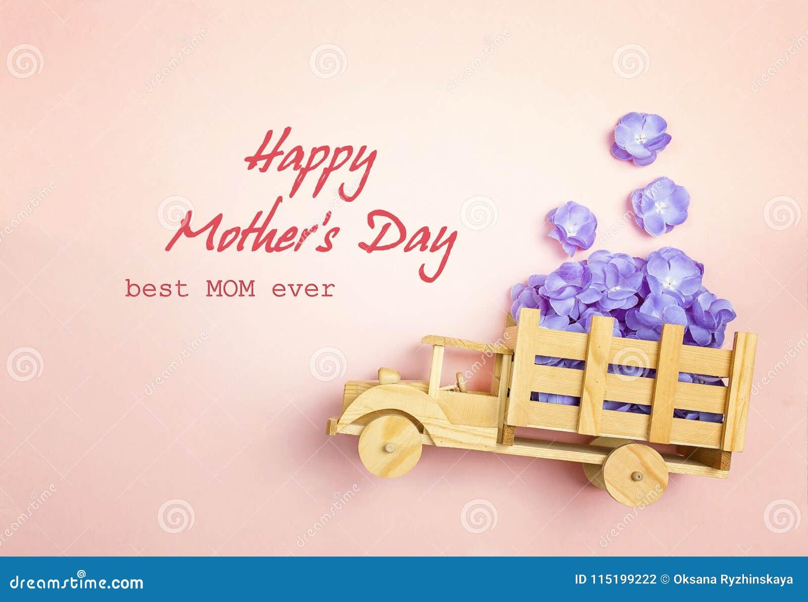 De groetbericht van de moedersdag met houten stuk speelgoed vrachtwagen met violet F