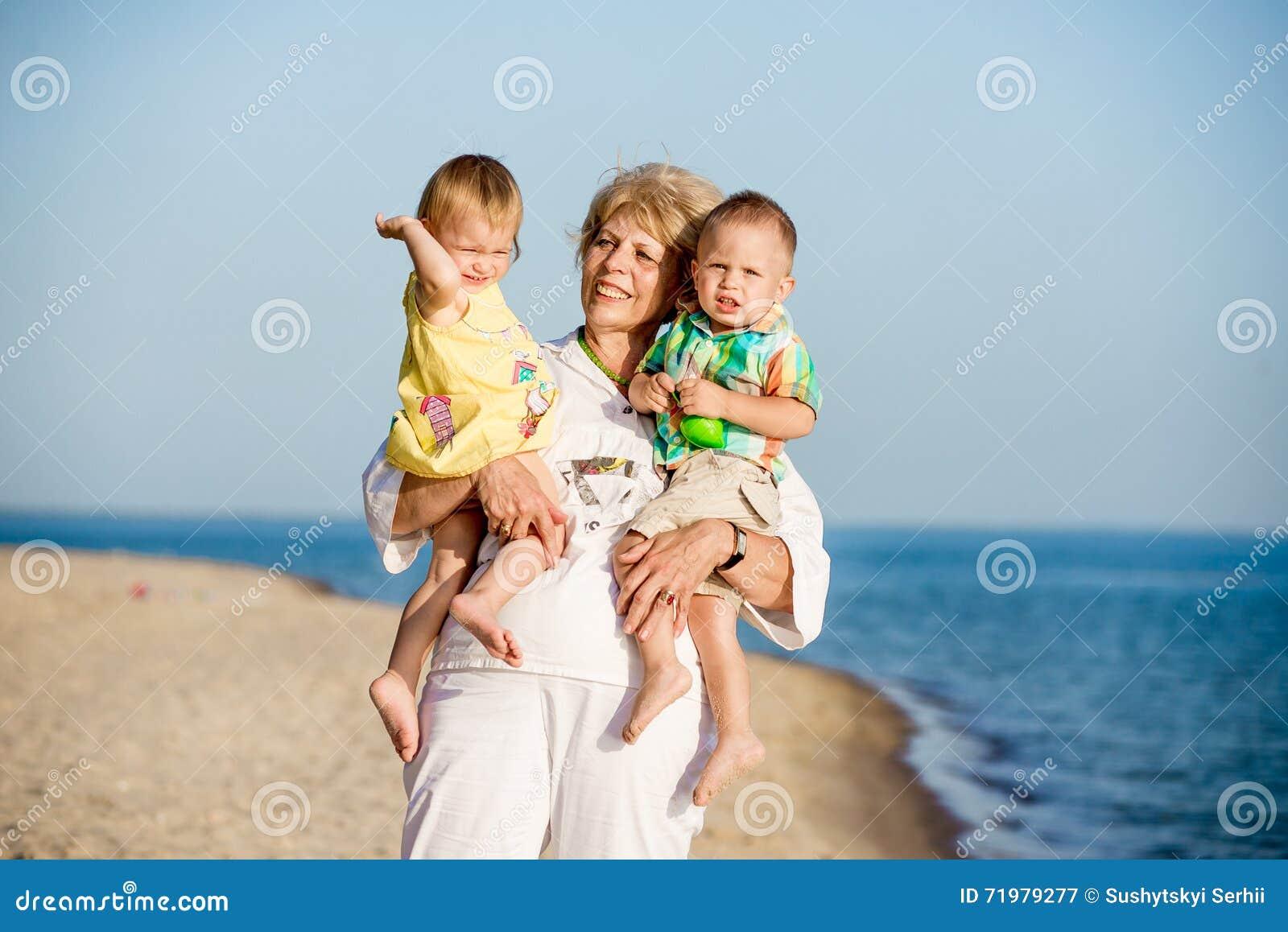 De grootmoeder houdt kleinzonen op handen