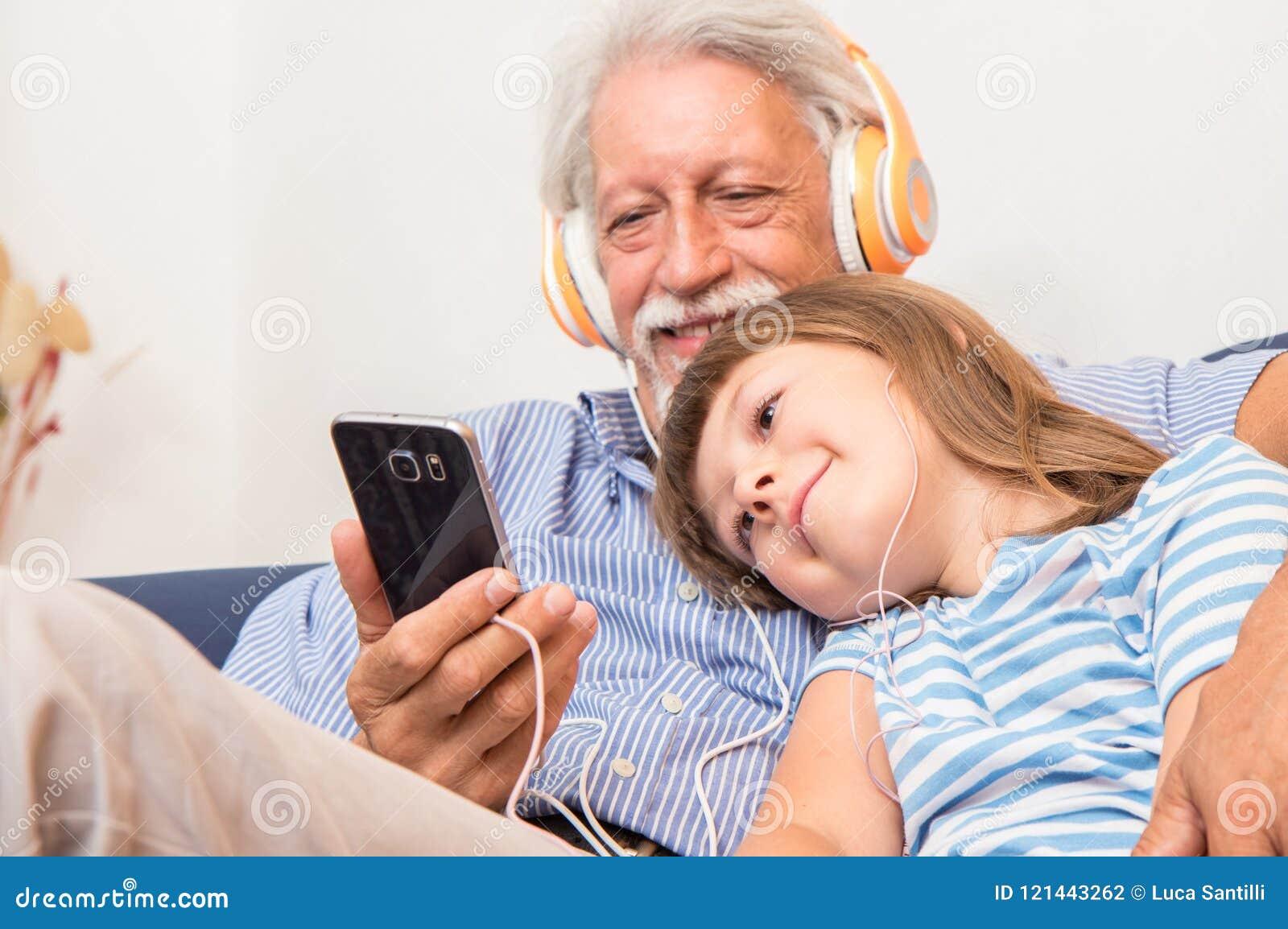 De grootvader en de kleinzoon met hoofdtelefoons luisteren aan muziek het koesteren