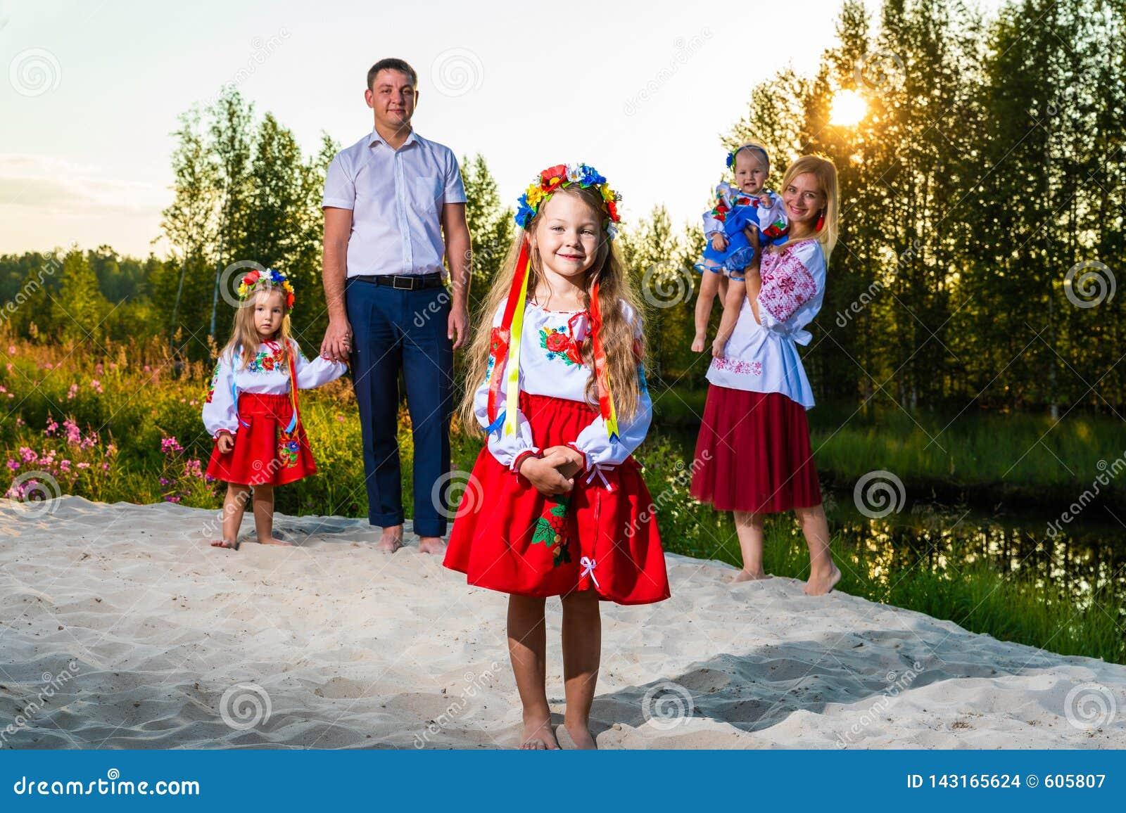 De grote familie in etnische Oekraïense kostuums zit op de weide, het concept een grote familie