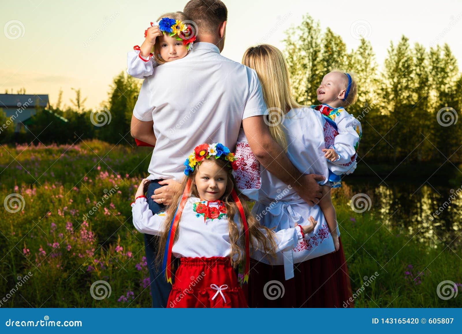De grote familie in de etnische Oekraïense kostuums zit op de weide, het concept een grote familie Achter mening