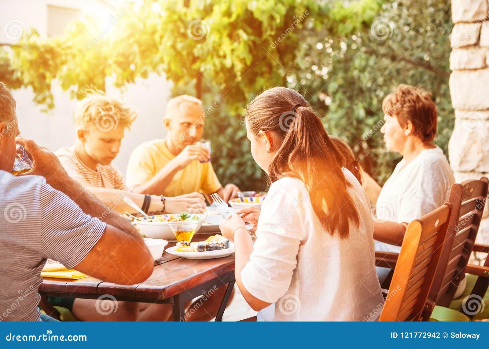 De grote familie heeft diner op open tuinterras