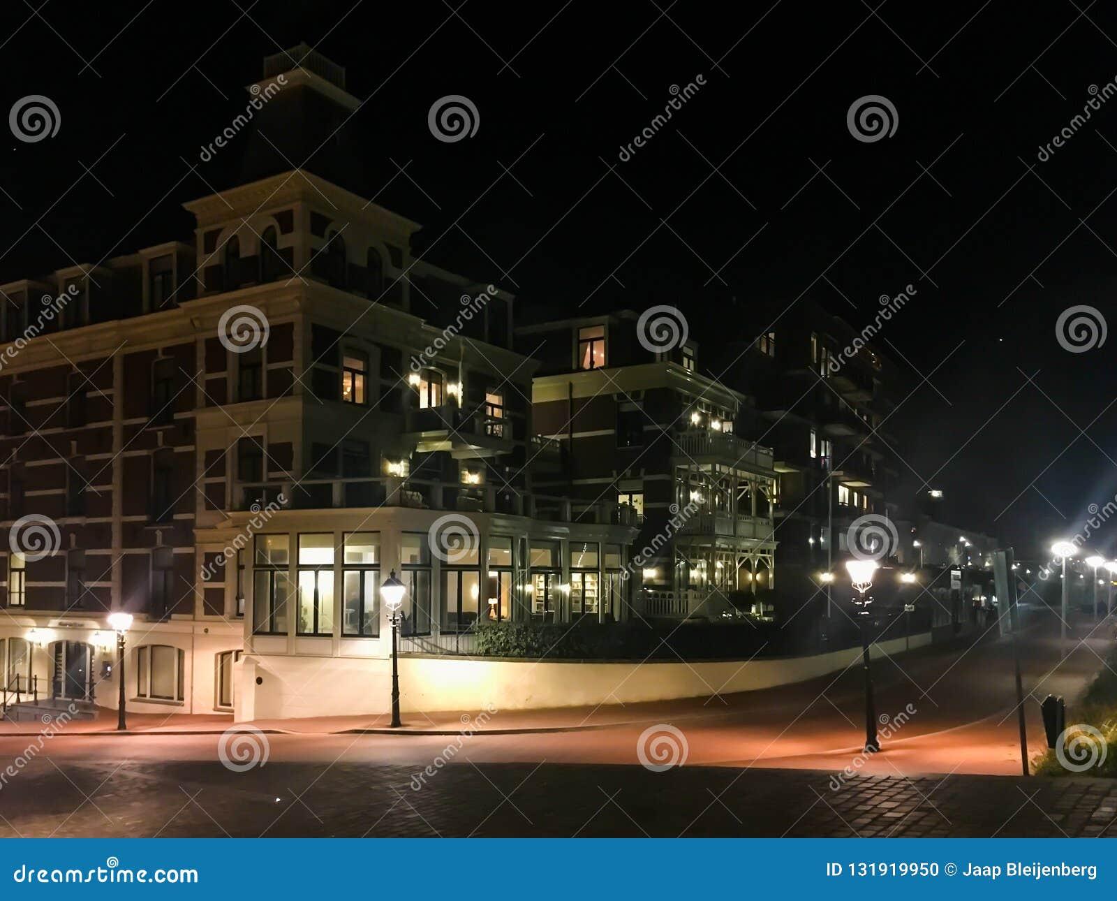 De grote flats complexe bouw met de weg van de stadsstraat en aangestoken lantaarnpalen in de populaire stad Scheveningen Nederla
